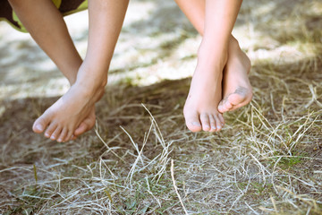 Closeup of two children legs barefoot on sunny countryside