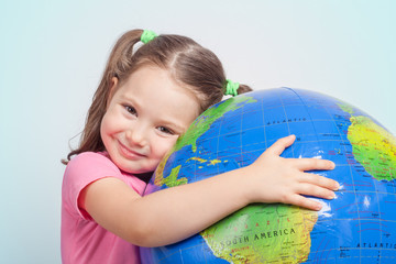 cute little girl hugging globe. save the earth concept.