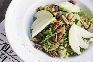 Healthy spinach and arugula salad with cilantro, dried figs, spiced almonds and apple served with a lite vinaigrette.