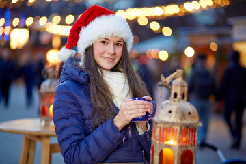 Young woman with santa hat on Christmas Market