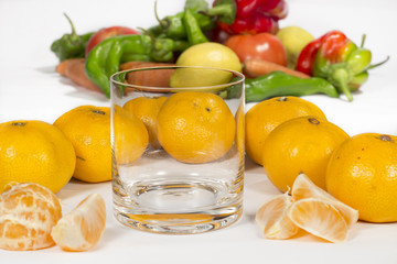 Empty glass cup next to several mandarins and tangerine segments. A bunch of different vegetables at background