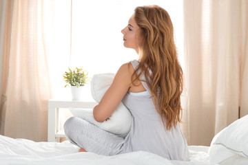 Young beautiful pensive woman sitting on her bed and holding her