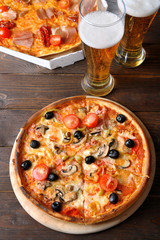 Pizza served with beer on wooden table