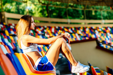 Girl in blue shorts sitting on stadium
