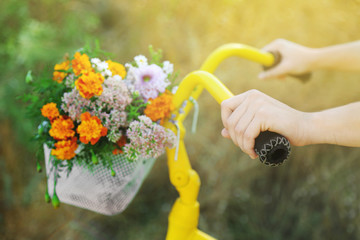 Beautiful yellow bicycle with bouquet of flowers in basket, outdoors