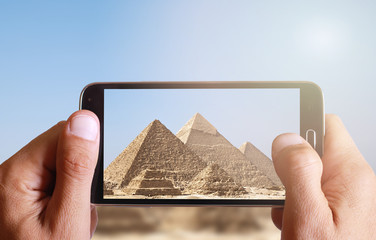 Male hand taking photo of Great pyramids in Giza with cell, mobile phone. Egypt holiday.