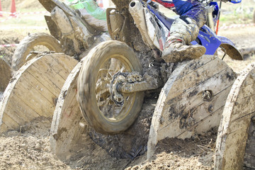 enduro bikes pass obstacle cable drums in track.