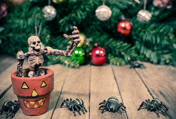 Funny Skeleton Sitting in Halloween Pumpkin Pot and Tiny Spiders on Wooden Background