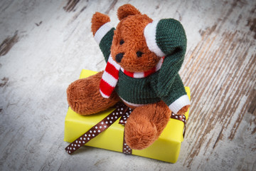 Teddy bear with yellow gift for Christmas or other celebration