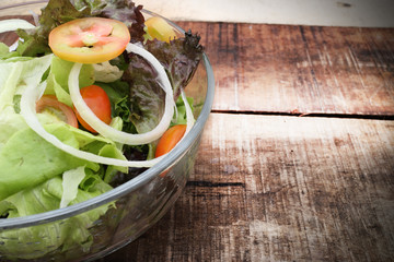 Fresh healthy salad on wooden table. View from above with copy space