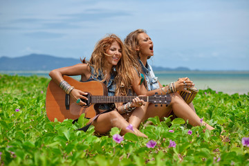 two beautiful hippie girls friends with guitar and drum on the b
