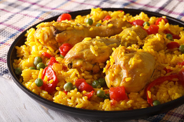 Paella with chicken meat and vegetables closeup. horizontal