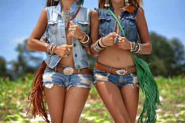 close up of beautiful hippie girls in denim clothes with green f