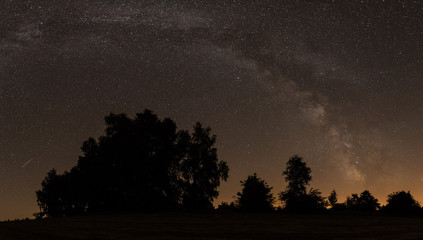 night sky panorama with milky way over trees silhouette
