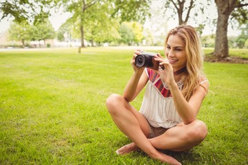 Woman taking picture while sitting on grass
