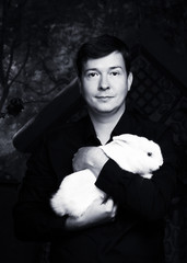Portrait of a man with a white rabbit on his hands