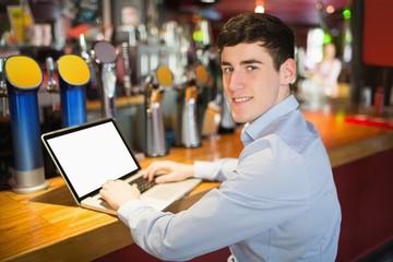 Portrait of happy man using laptop