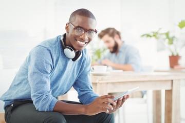 Portrait of smiling man with headphones using digital tablet