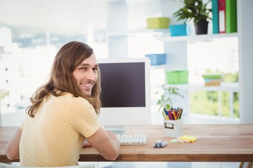 Portrait of happy hipster working at computer desk