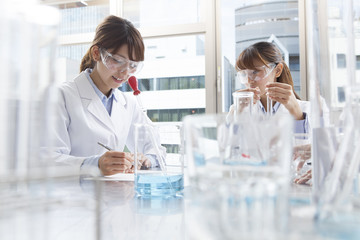 Women are studying it with a white coat and goggles