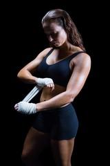 Beautiful athlete tying bandage on hand