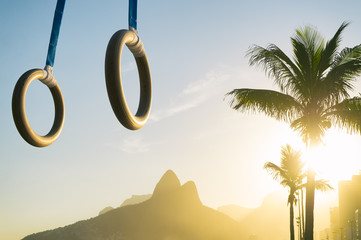 Gymnast rings hanging in golden sunset light above Ipanema Beach at the Rio de Janeiro, Brazil mountain skyline