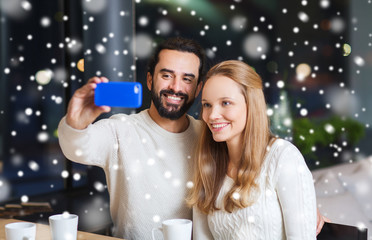 happy couple with smartphone  and coffee at cafe