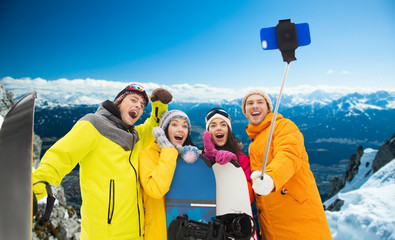 happy friends with snowboards and smartphone