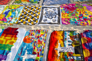 Beach blanket sarongs known locally as canga spread out in colorful display along the Ipanema Beach boardwalk