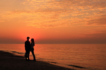 Silhouettes of couples of young people at sunset on the sea