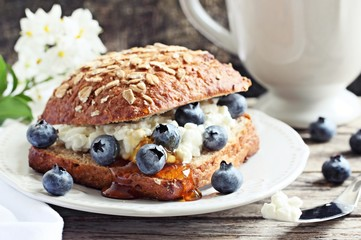 Wholegrain bun bun with cottage cheese, blueberries and honey. Toned image.Selective focus