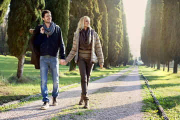 couple walking in the leafy avenue in an autumn day