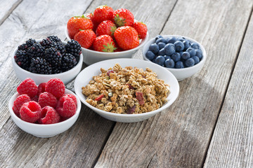 muesli and garden berries on wooden background