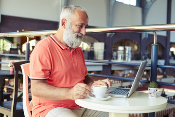 man with cup of coffee working