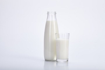 Open bottle and glass of milk on white background.