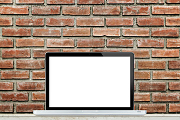 Laptop computer on table with brick wall background.