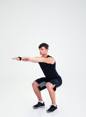 Fitness man doing squatting exercises