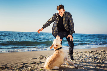young caucasian male playing with labrador on beach during sunri