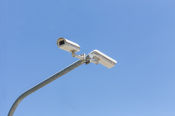 Two security camera on blue sky