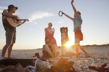 Friends playing music together on a beach