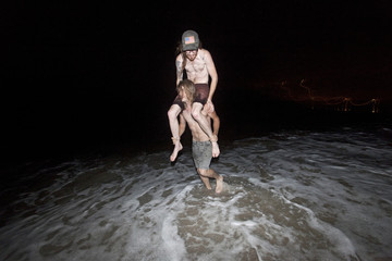 Friends playing on a beach at night