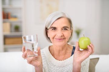 seniorin hält ein glas wasser und einen grünen apfel in der hand