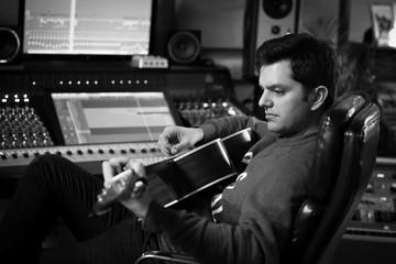 Man playing guitar in recording studio