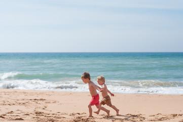 Two boys running along the beach