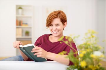lächelnde junge frau liest ein buch auf dem sofa