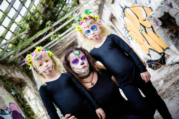 Woman and twin girls with sugar skull makeup