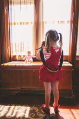 Girl taking a photo of her toy doll