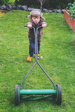 Portrait of a boy mowing lawn