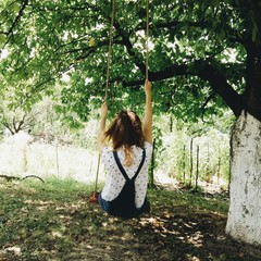 Rear view of a woman sitting on a swing