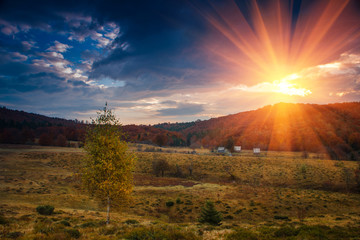 Panoramic view of the dramatic sunset in the autumn mountains.